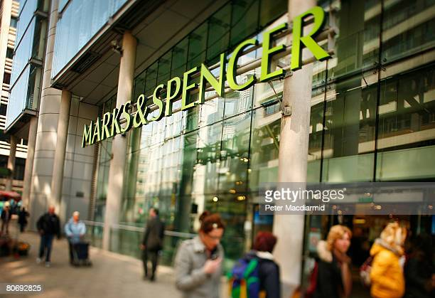 Customers walk near a Marks and Spencer shop in the City on April 16 2008 in London England The United Kingdom's financial outlook still looks gloomy...