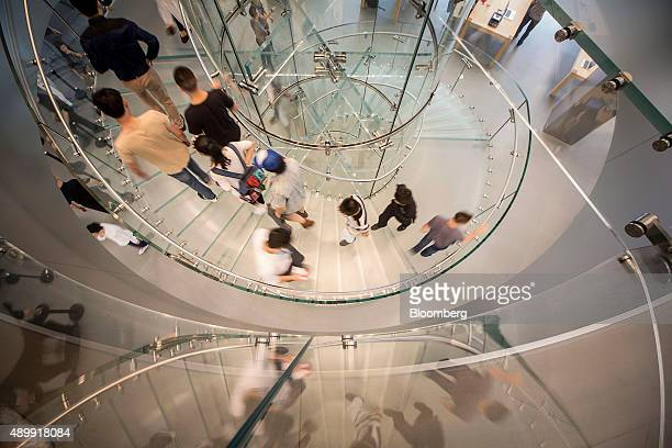 Customers walk on a staircase at the Apple Inc store during the sales launch of the iPhone 6s and iPhone 6s Plus at the IAPM shopping mall in...