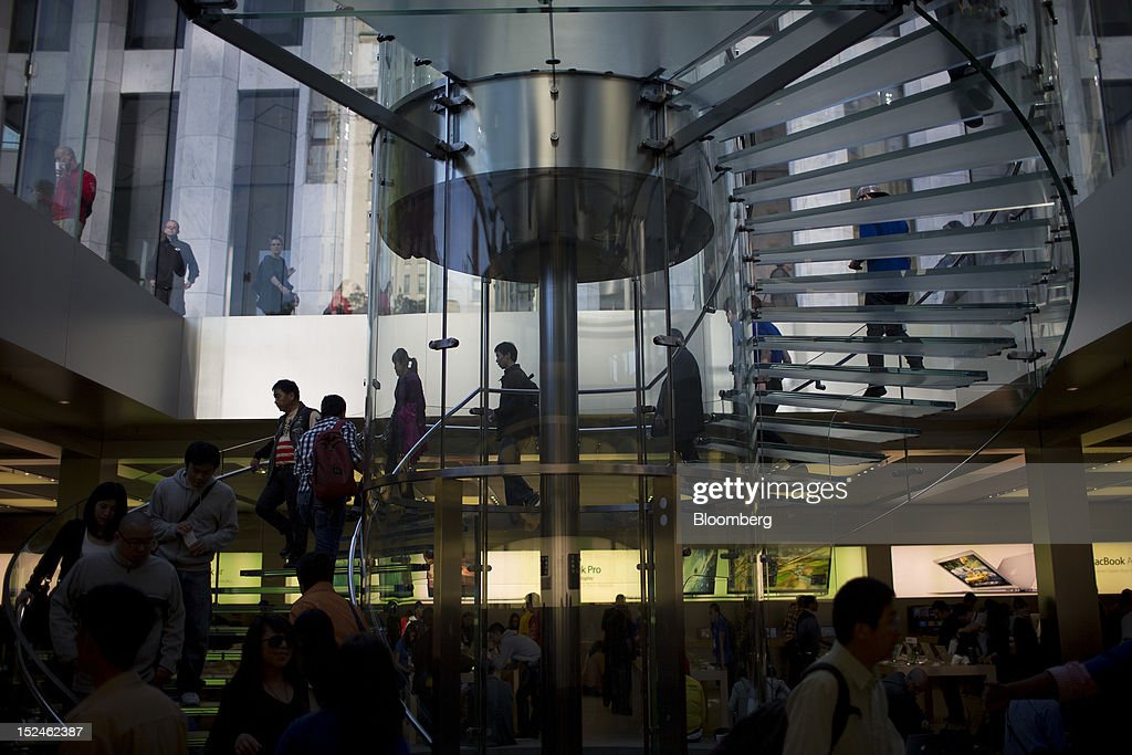 Customers walk on a staircase inside the Fifth Avenue store during the first day of in store sales for the new Apple Inc. iPhone 5 in New York, U.S., on Friday, Sept 21, 2012. Apple Inc. is poised for a record iPhone 5 debut and may not be able to keep up with demand as customers lined up in Sydney, Tokyo, Paris and New York to pick up the latest model of its top-selling product. Photographer: Scott Eells/Bloomberg via Getty Images