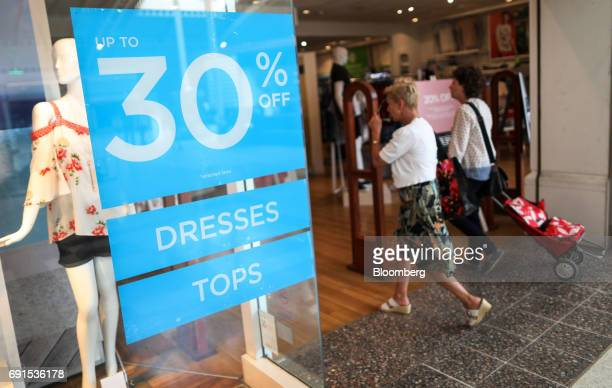 Customers walk past a sign offering a 30 percent discount as they enter a clothing retail store in Aylesbury UK on Friday June 2 2017 AUK...