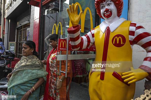 Customers walk past a statue of Ronald McDonald as they exit a McDonald's Corp restaurant operated by Hardcastle Restaurants Pvt in Bangalore India...