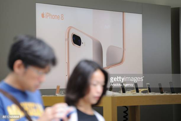 Customers walk past a stokiest as new iPhone 8 and plus models are displayed at a telecom shop in Omotesando Avenue in Tokyo Japan on September 22...