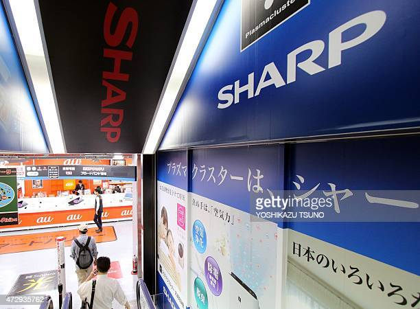 Customers walk past advertisements for Japanese electronics manufacturer Sharp at an electrics shop in Tokyo on May 11 2015 Sharp lost a quarter of...