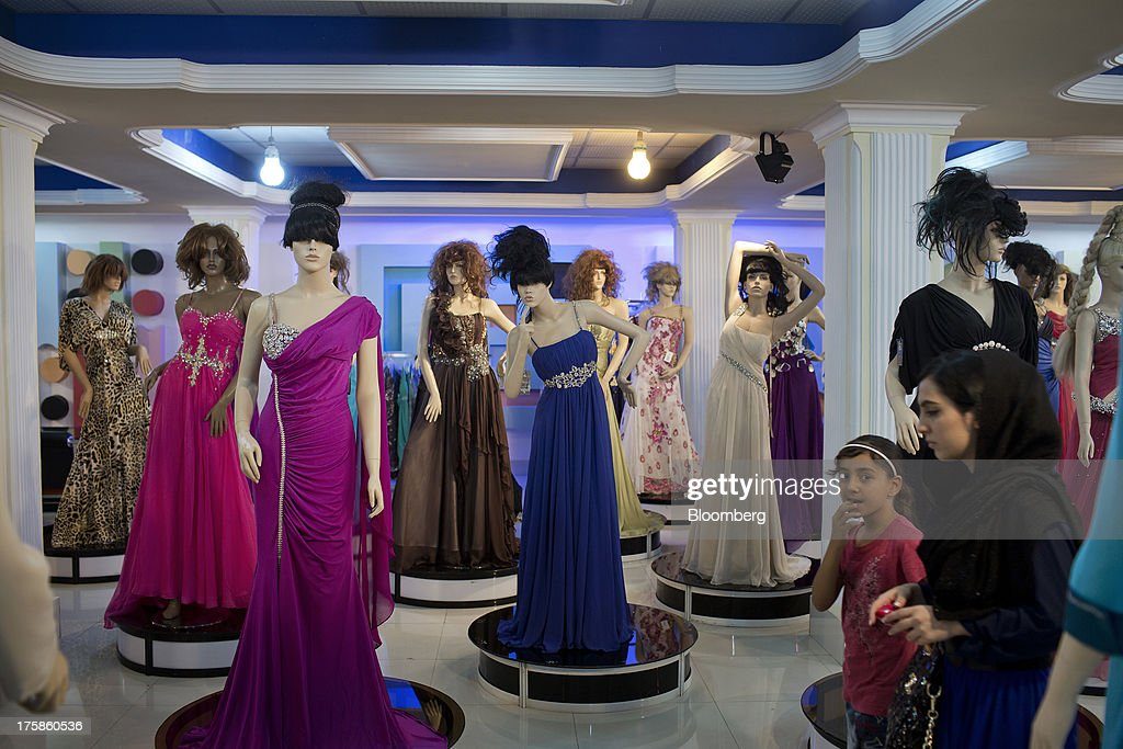 Customers walk past mannequins displaying evening wear inside a department store in the Faisal Business Center in Kabul, Afghanistan, Wednesday, Aug. 7, 2013. A smooth U.S. exit from Afghanistan will depend on Pakistans cooperation with the logistical pullout, as well as its backing for peace talks in neighboring Afghanistan and an end to any support for extremist proxies operating there. Photographer: Victor J. Blue/Bloomberg via Getty Images