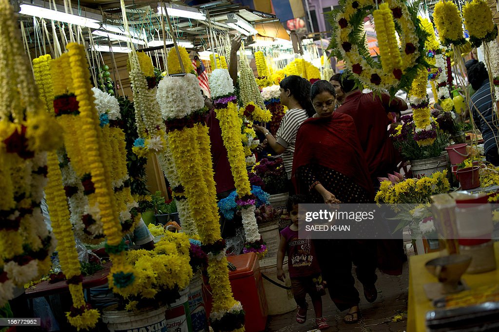 Customers walk through a flower market in the Brickfields area, also known as Little India, in Kuala Lumpur on November 20, 2012. Malaysia's economy grew a better-than-expected 5.2 percent in the third quarter as domestic demand continued to compensate for a slowdown in exports, the government said recently. AFP PHOTO / Saeed KHAN