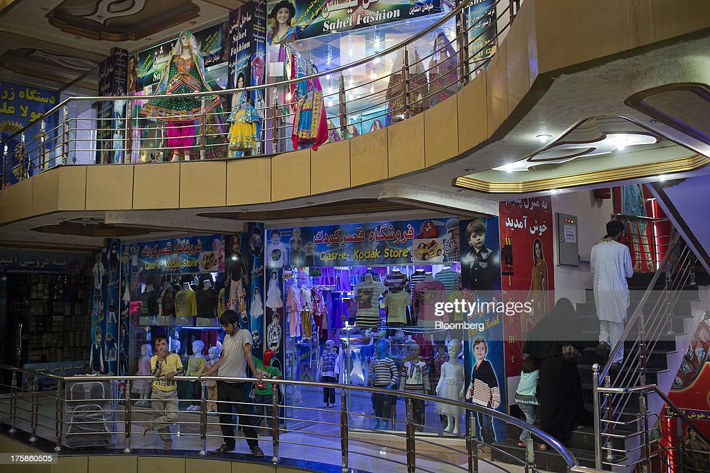 Customers walk through Noor Shopping Center in Kabul, Afghanistan, Wednesday, Aug. 7, 2013. A smooth U.S. exit from Afghanistan will depend on Pakistans cooperation with the logistical pullout, as well as its backing for peace talks in neighboring Afghanistan and an end to any support for extremist proxies operating there. Photographer: Victor J. Blue/Bloomberg via Getty Images