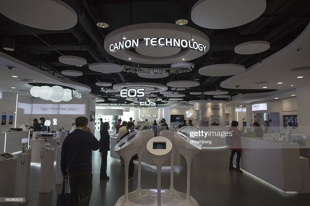 Customers walk through the Canon Inc. showroom in Hong Kong, China, on Tuesday, Jan. 29, 2013. Canon, the world's largest camera maker, forecast profit will rise 14 percent this year amid a weaker yen and the withering of a boycott of Japanese goods in China. Photographer: Jerome Favre/Bloomberg via Getty Images