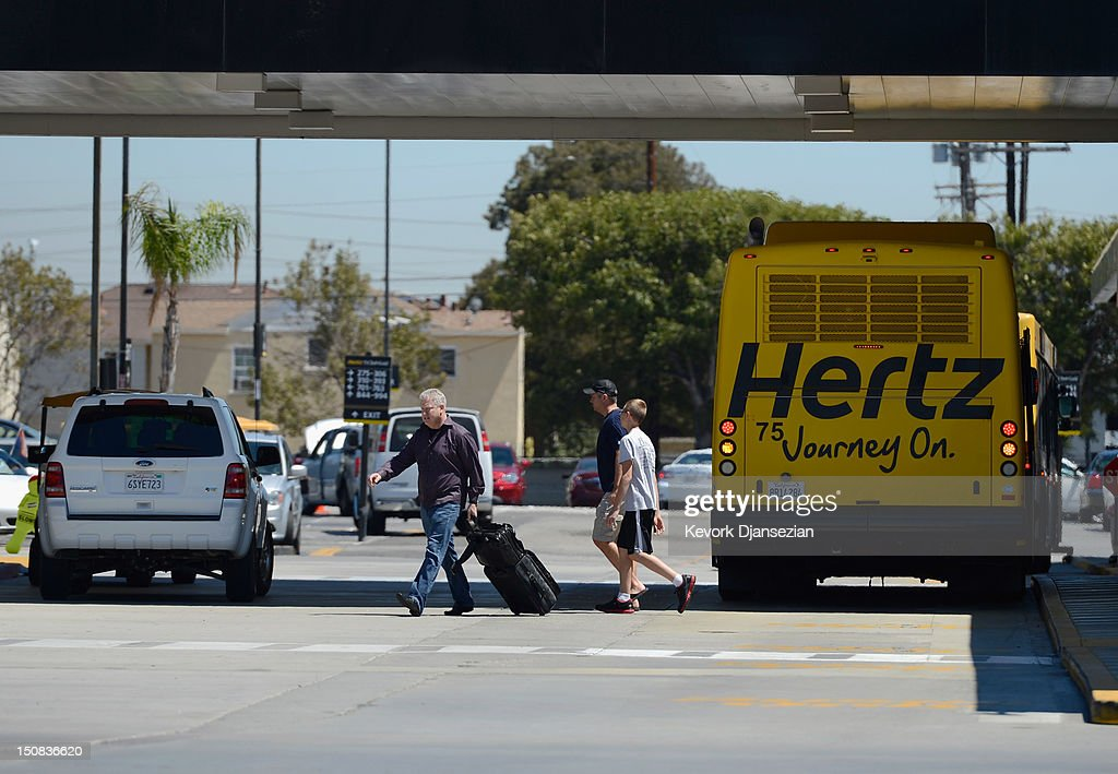 Customers walk to their cars at Hertz Global Holdings car rental Los Angeles International Airport branch August 27, 2012 in Los Angeles, California. Two major rental car companies agreed to merge as Hertz Global Holdings announced it is acquring Dollar Thrifty Automotive Group for $2.3 billion.