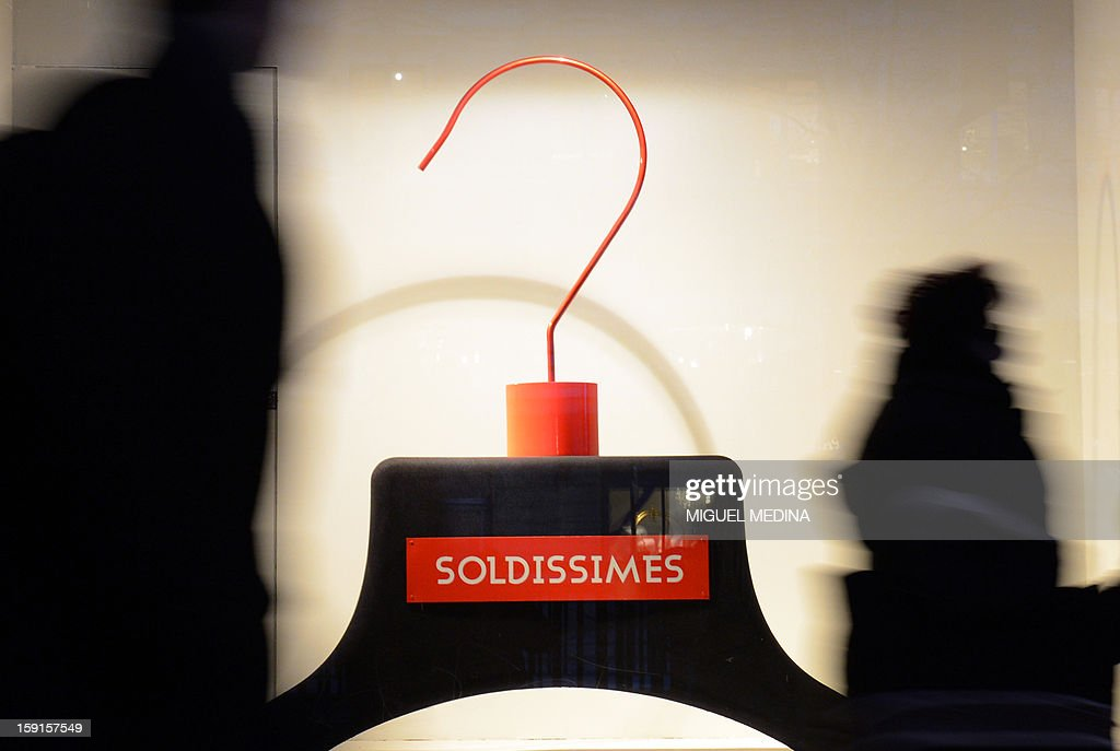 Customers walks past a shop window with a giant sign announcing sales at the Galeries Lafayette department store in Paris, on January 9, 2013, during the official start of winter sales.