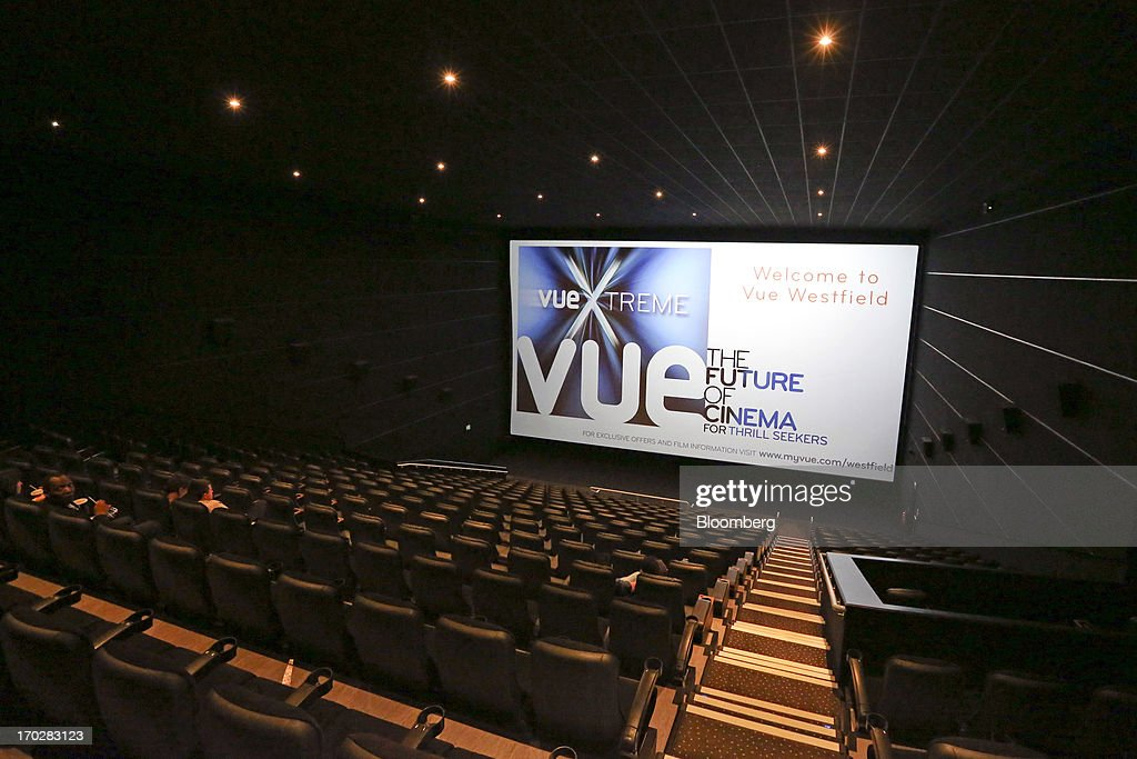 Customers watch a an advertisement on a screen before the start of a 3-D film inside a Vue Cinema, operated by Vue Entertainment Ltd., at the Westfield Stratford City retail complex in London, U.K., on Tuesday, June 4, 2013. Vue Entertainment, the U.K. cinema chain bought by private equity firm Doughty Hanson & Co., are continuing to expand in Europe, recently acquiring Poland's second-largest cinema chain Multikino. Photographer: Chris Ratcliffe/Bloomberg via Getty Images