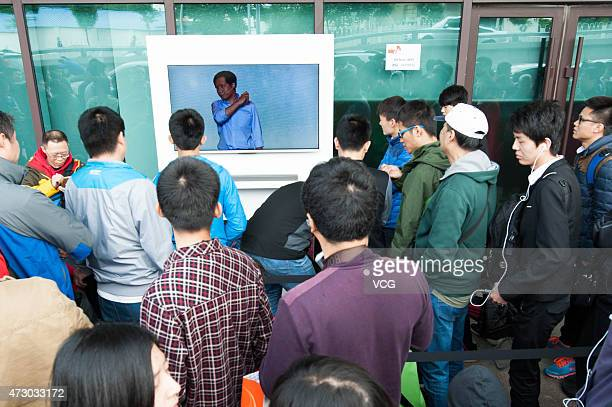 Customers watch promotional video from Xiaomi's chairman Lei Jun before the high configuration Xiaomi Note to be on sale at a Xiaomi experience store...