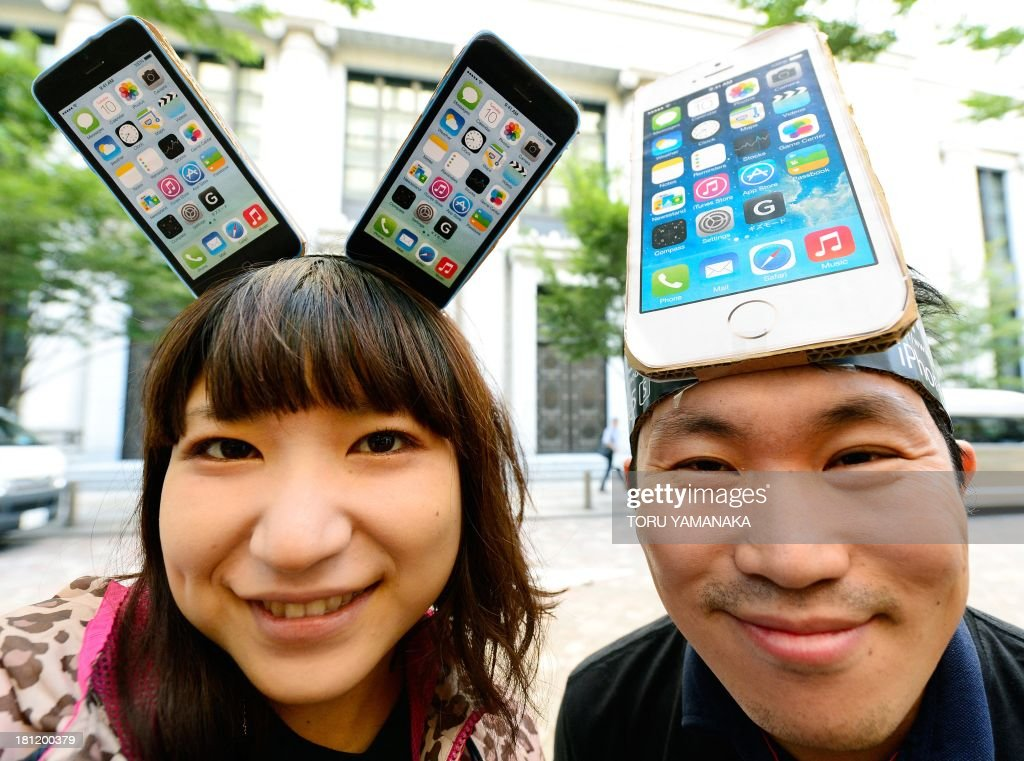 Customers wearing hand-made iPhone headpieces smile as they wait to purchase Apple's new iPhone 5 outside an outlet of Japan's biggest mobile carrier, NTT Docomo in Tokyo on September 20, 2013. Apple's new iPhone 5s and 'cheap' 5C models on September 20 went on sale in Japan. AFP PHOTO/Toru YAMANAKA