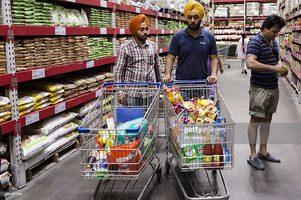 Customers with shopping carts browse food items at a Walmart India Pvt. Best Price Modern Wholesale store in the town of Zirakpur on the outskirts of Chandigarh, Punjab, India, on Tuesday, June 10, 2014. India's consumer price index (CPI) figures and wholesale price inflation figures for May are scheduled for release on June 12 and 16 respectively. Photographer: Udit Kulshrestha/Bloomberg via Getty Images