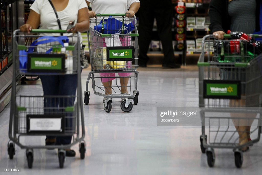 Customers with shopping carts during the grand opening of a Wal-Mart Stores Inc. location in the Chinatown neighborhood of Los Angeles, California, U.S., on Thursday, Sept. 19, 2013. Wal-Mart Stores Inc. will phase out 10 chemicals it sells in favor of safer alternatives and disclose the chemicals contained in four product categories, the company announced Sept. 12. Photographer: Patrick T. Fallon/Bloomberg via Getty Images