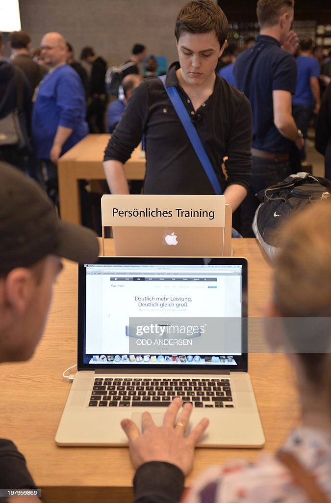 Customers work on 'Apple' laptops at the personal training desk during the opening of the first 'Apple' store in Berlin at the Kurfuerstendamm on May 3, 2013.