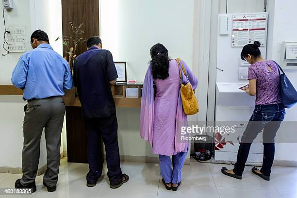 Customers write cheque deposit slips inside an Axis Bank Ltd branch in Mumbai India on Thursday Jan 16 2014 Axis Bank said net income in the third...