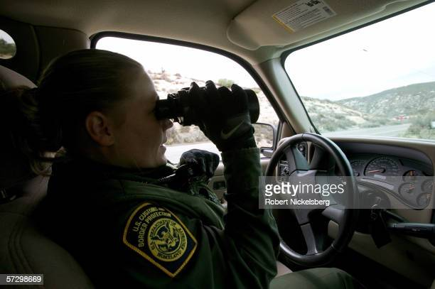 A Customs and Border Patrol agent uses her binoculars to follow Mexican aliens running north from pursuing CBP agents on March 6 2006 in Campo...