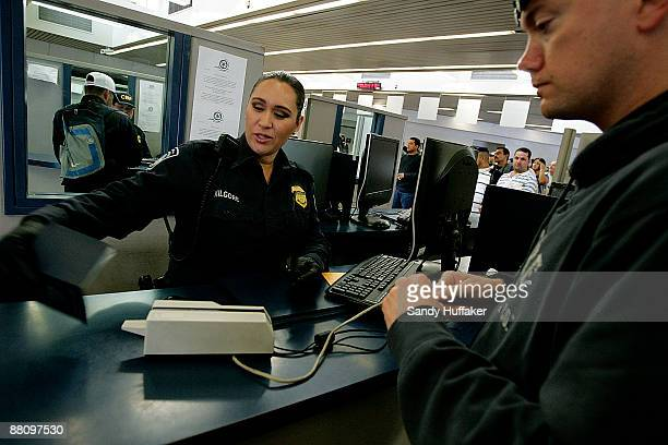 Customs and Border Protection agent Desiree Kilgore checks a passport from a pedestrian crossing into the United States from Mexico at the San Ysidro...
