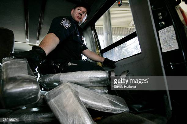 Customs and Border Protection agent Ian Bow pulls out bricks of Marijuana from a van seized at the US Port of Entry December 15 2006 in San Ysidro...