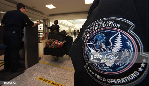 Customs and Border Protection Officer checks the declarations of a international air traveler as she is processed into the United States in the US...