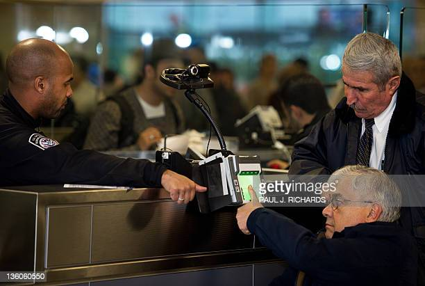 Customs and Border Protection Officer directs an international air traveler in a wheel chair how to use the biometric scanner as he enters the United...