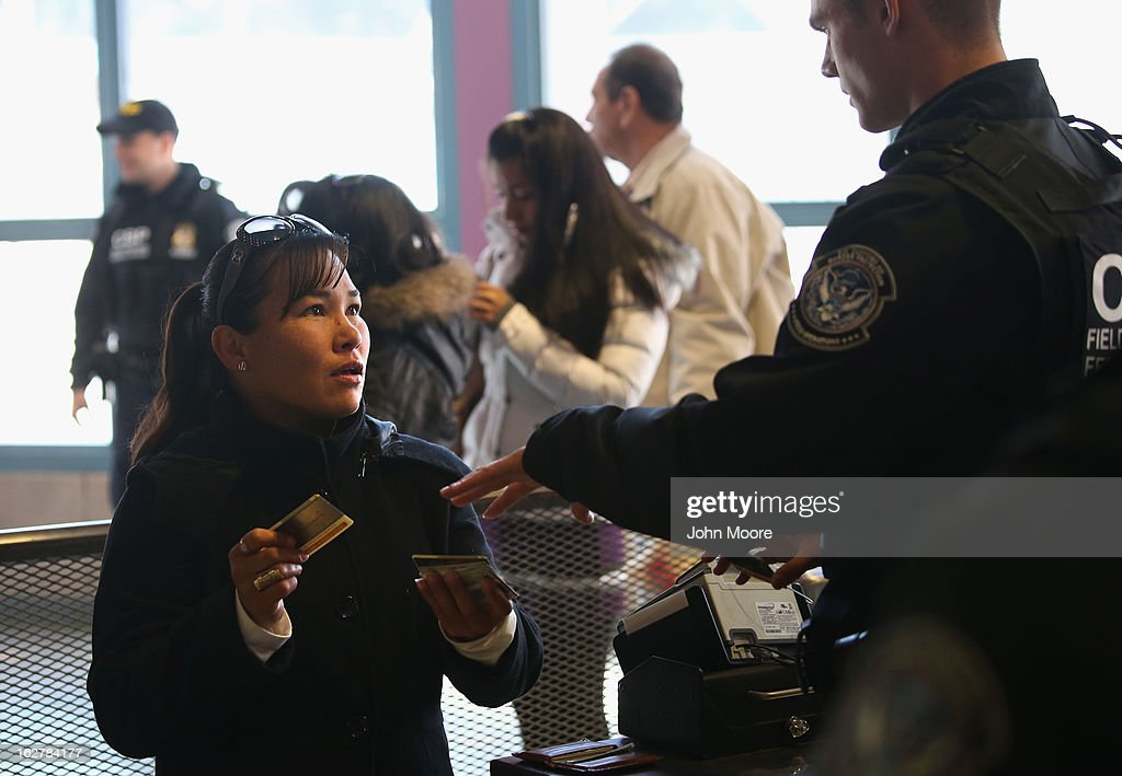S. Customs and Border Protection officer from the Office of Field Operations (OFO), checks identifications of people crossing from Mexico into the United States on February 26, 2013 in Nogales, Arizona. Some 15,000 people cross between Mexico and the United States each day in Nogales, Arizona's busiest border crossing.