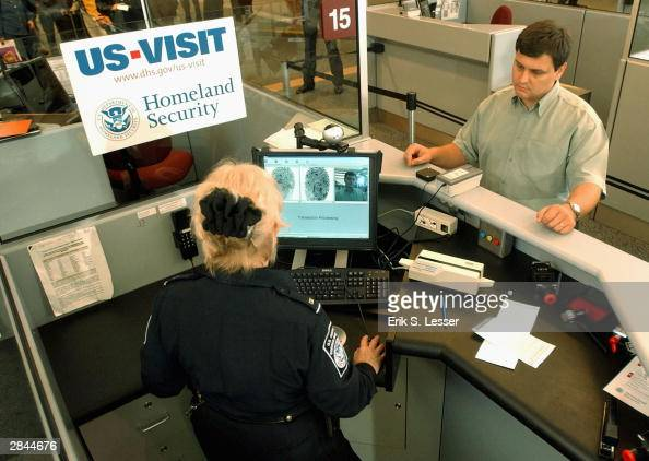 Customs and Border Protection officer Mary Armbrust uses the new USVISIT biometric program on visitor Sergio Pajedas of Brazil at HartsfieldJackson...