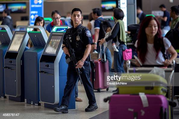 S Customs and Border Protection officer watches over travelers at Los Angeles International Airport on July 2 2016 in Los Angeles California Security...