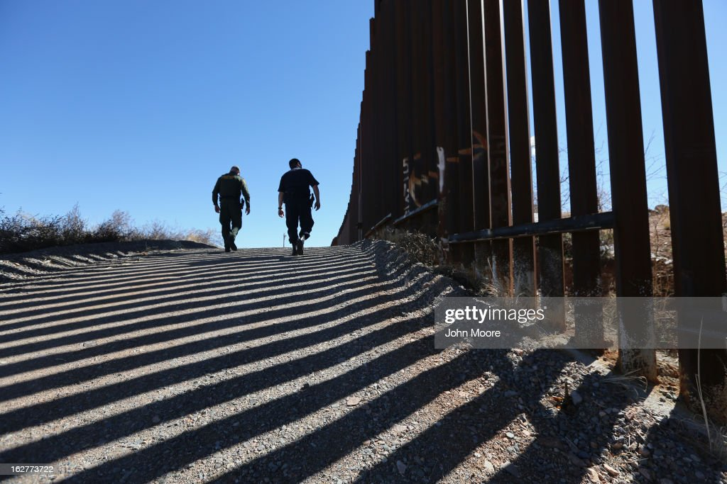 U.S. Customs and Border Protection personnel walk along a section of the recently-constructed fence at the U.S.-Mexico border on February 26, 2013 in Nogales, Arizona. The newest generation of fencing allows Border Patrol agents to see through the fence and is harder to scale from the Mexican side.