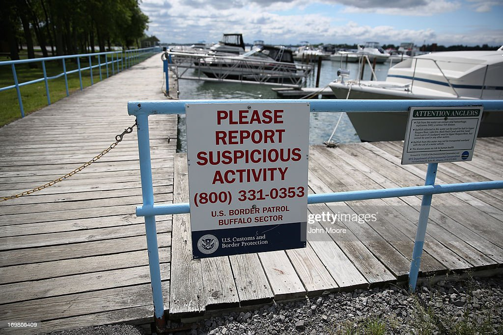 A U.S. Customs and Border Protection sign hangs on a fence at a marina on the Niagara River which forms the U.S.-Canada border on June 3, 2013 in Beaver Island State Park, New York. U.S. Customs and Border Protection, which includes the Border Patrol, monitors the 5,525 mile long border, including Alaska, forming the longest international border between two countries in the world.