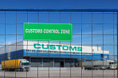 The green plate with white letters, the customs control zone, is fixed on the fence in front of the logistics complex with customs clearance services and warehouse storage of goods.