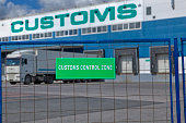 The truck is unloaded at a customs warehouse, behind a fence with a green sign, a customs control zone.