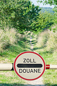 Tollgate with demarcation and road sign customs office between two countries.