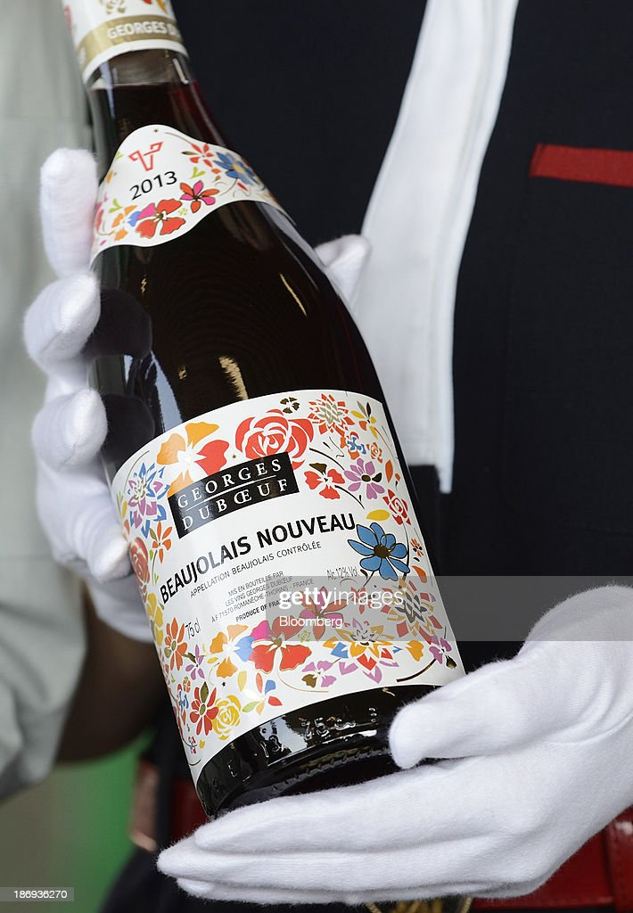 A customs officer holds a bottle of Georges Duboeuf Beaujolais Nouveau wine during an inspection at Haneda Airport in Tokyo, Japan, on Tuesday, Nov. 5, 2013. Japanese appetite for Beaujolais Nouveau has made the country the largest buyer of the young wine outside France, purchasing three times the U.S., the next biggest importer. Photographer: Akio Kon/Bloomberg via Getty Images