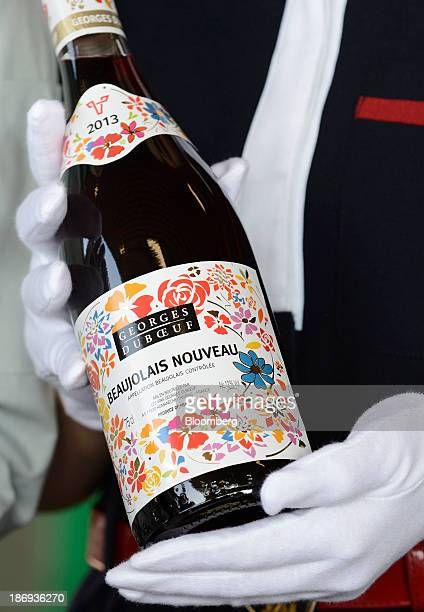 A customs officer holds a bottle of Georges Duboeuf Beaujolais Nouveau wine during an inspection at Haneda Airport in Tokyo Japan on Tuesday Nov 5...