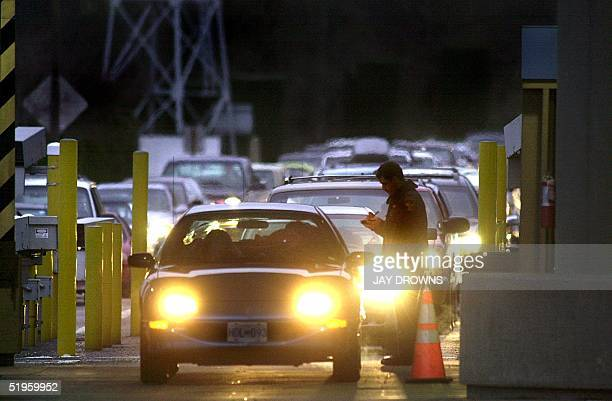 Customs officer is on duty as cars line up to pass through the customs station at Blaine Washington to enter Surrey Canada 20 December 1999 as the...