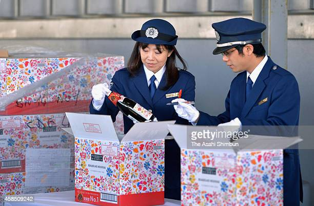 Customs officers check bottles of Beaujolais nouveau at Tokyo International Airport on November 4 2014 in Tokyo Japan The wine is released from an...
