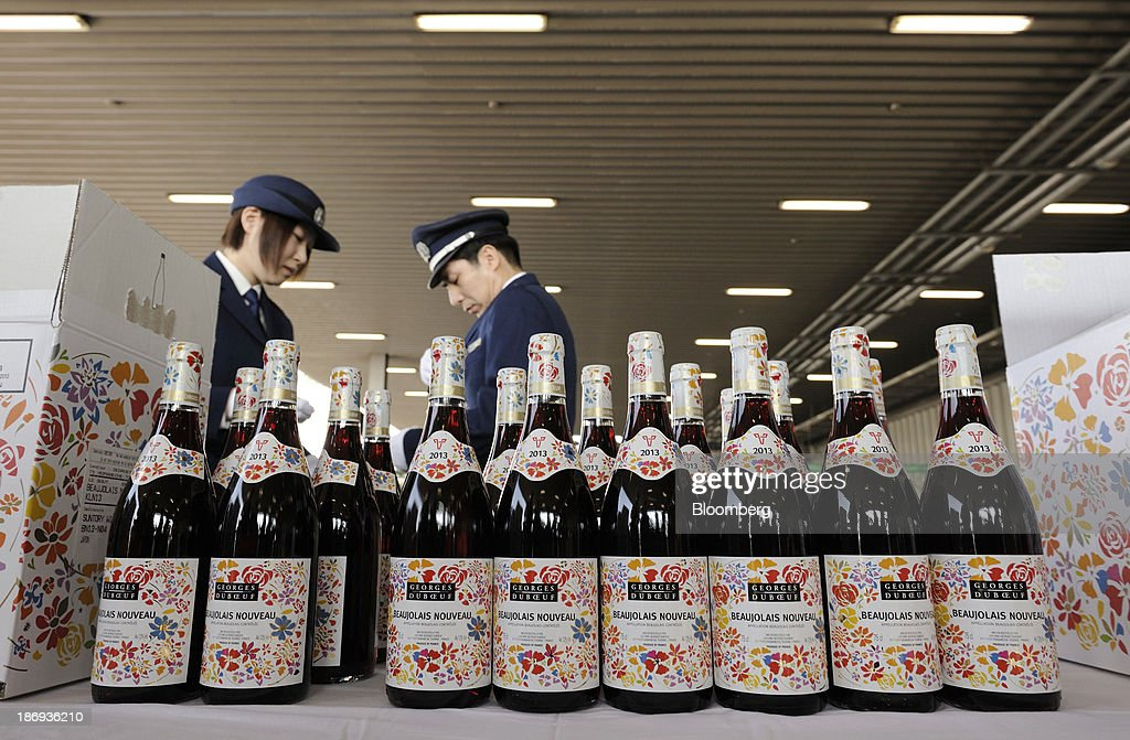Customs officers inspect bottles of Georges Duboeuf Beaujolais Nouveau wine at Haneda Airport in Tokyo, Japan, on Tuesday, Nov. 5, 2013. Japanese appetite for Beaujolais Nouveau has made the country the largest buyer of the young wine outside France, purchasing three times the U.S., the next biggest importer. Photographer: Akio Kon/Bloomberg via Getty Images