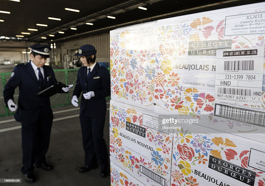 Customs officers stand near boxes of Georges Duboeuf Beaujolais Nouveau wine at Haneda Airport in Tokyo, Japan, on Tuesday, Nov. 5, 2013. Japanese appetite for Beaujolais Nouveau has made the country the largest buyer of the young wine outside France, purchasing three times the U.S., the next biggest importer. Photographer: Akio Kon/Bloomberg via Getty Images