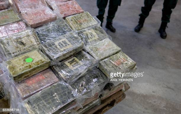 Customs officers stand next to a forklift truck that carries a pallet of cocaine packets on February 3 2017 in Hamburg The 717 kilos of cocaine with...