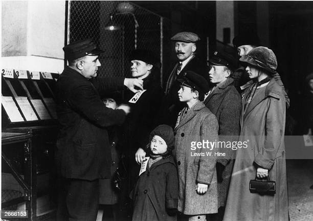 A customs official attaches labels to the coats of a German immigrant family at the Registry Hall on Ellis Island New York City