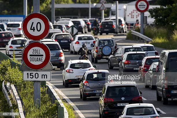 A 'customs' sign is seen as cars queue ahead of the border between Switzerland and France on June 6 2014 in Perly near Geneva AFP PHOTO / FABRICE...