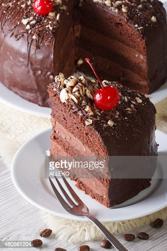 Cut a piece of chocolate cake with cherries. Vertical close-up : Stock Photo