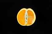 cut half an orange on a wooden table on a dark background