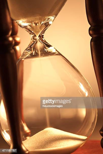 Cut image of sand flowing through hour glass