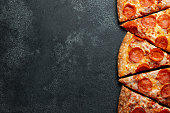 Cut into slices delicious fresh pizza with sausage pepperoni and cheese on a dark background. Top view with copy space for text. Pizza on the black concrete table. flat lay.