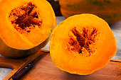 Cut into two parts ripe pumpkin, orange pulp and fiber in the core, a knife on a wooden kitchen Board.
