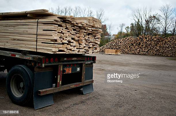 Cut lumber sits on a truck near a large pile of unprocessed logs outside the Nicolet Hardwoods Corp lumber mill in Laona Wisconsin US on Wednesday...