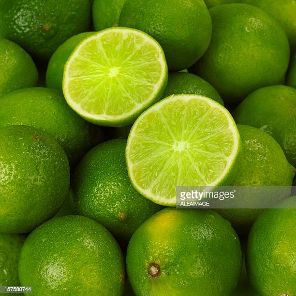 A cut open lime atop a pile of fresh limes