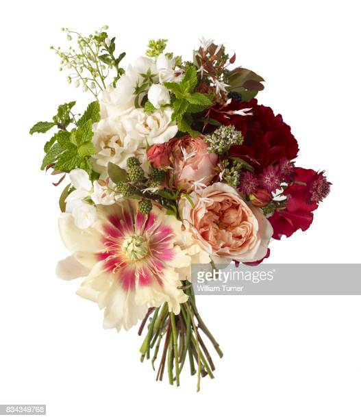 A cut out image of a bouquet or bunch of flowers including peony, rose, astrantia, mint and bramble